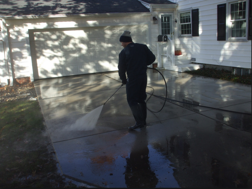 pressure washing a driveway for a residential home.